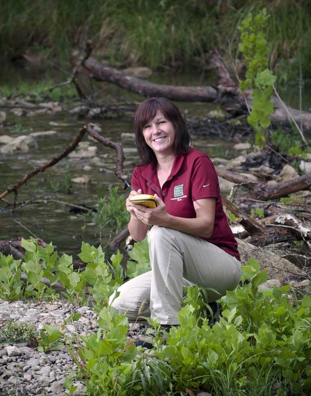 A female stream ecologist kneeling in a stream studying aquatic animal and plant life and doing research studies, an image from Working and Careers in Water and Aquatic Science from the book Texas Aquatic Science by author Rudolph Rosen. Photo credit: Texas Parks and Wildlife Department.