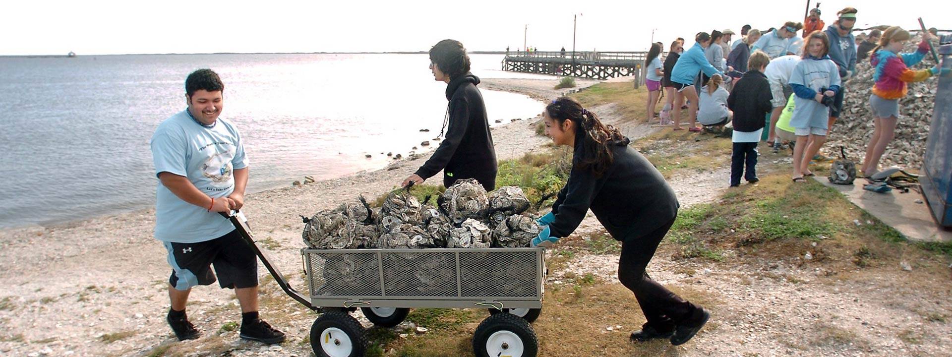 Photo of Texas aquatic science field trip showing students volunteering and having fun restoring oysters in Corpus Christi Bay, from the book Texas Aquatic Science by Rudolph Rosen. Photo credit: Corpus Christi Caller-Times.